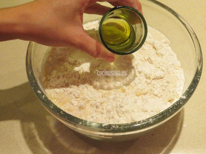 Añadir aceite a la mezcla de harina para elaborar la masa para la preparación de la rosca de pan