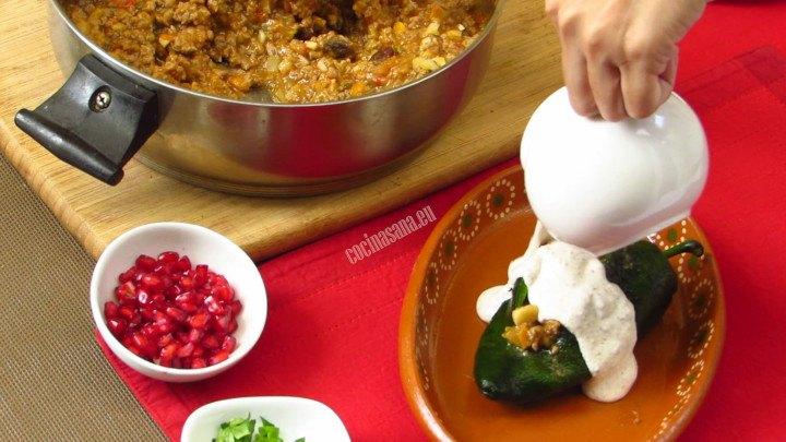 Cubrir el Chile con la salsa en nogada para colocar el resto de los ingredientes