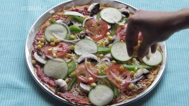 Agregar los ingredientes a la pizza, colocar el tomate, el calabacín y el resto de los ingredientes.
