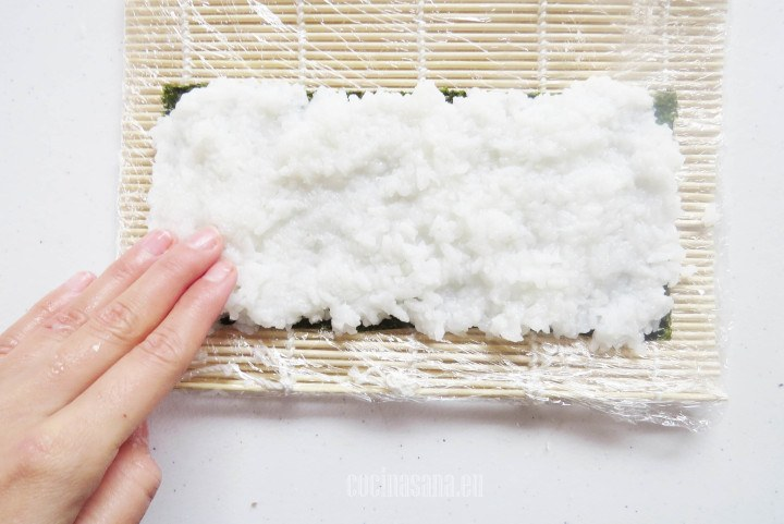 Cubrir el Alga nori con el arroz para sushi y formar una cama uniforme con el.
