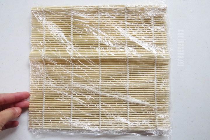 Colocar el film o papel plástico sobre el Makisu o esterilla de madera para evitar que se peguen los sushis.