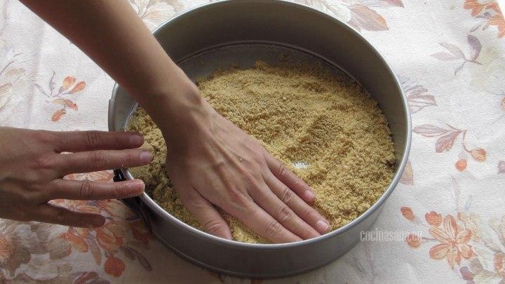 Añadir la galleta al molde y presionar ligeramente con tus manos o una cuchara para que se compacte y puedas formar la costra del pastel.