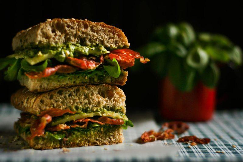 Sandwich de prosciutto crocante, con gruyere, rúcula y pesto de albahaca