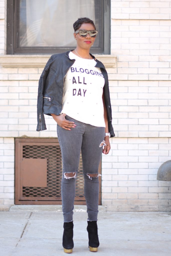 black moto jacket burnout tshirt ripped grey jeans black ankle boots standing