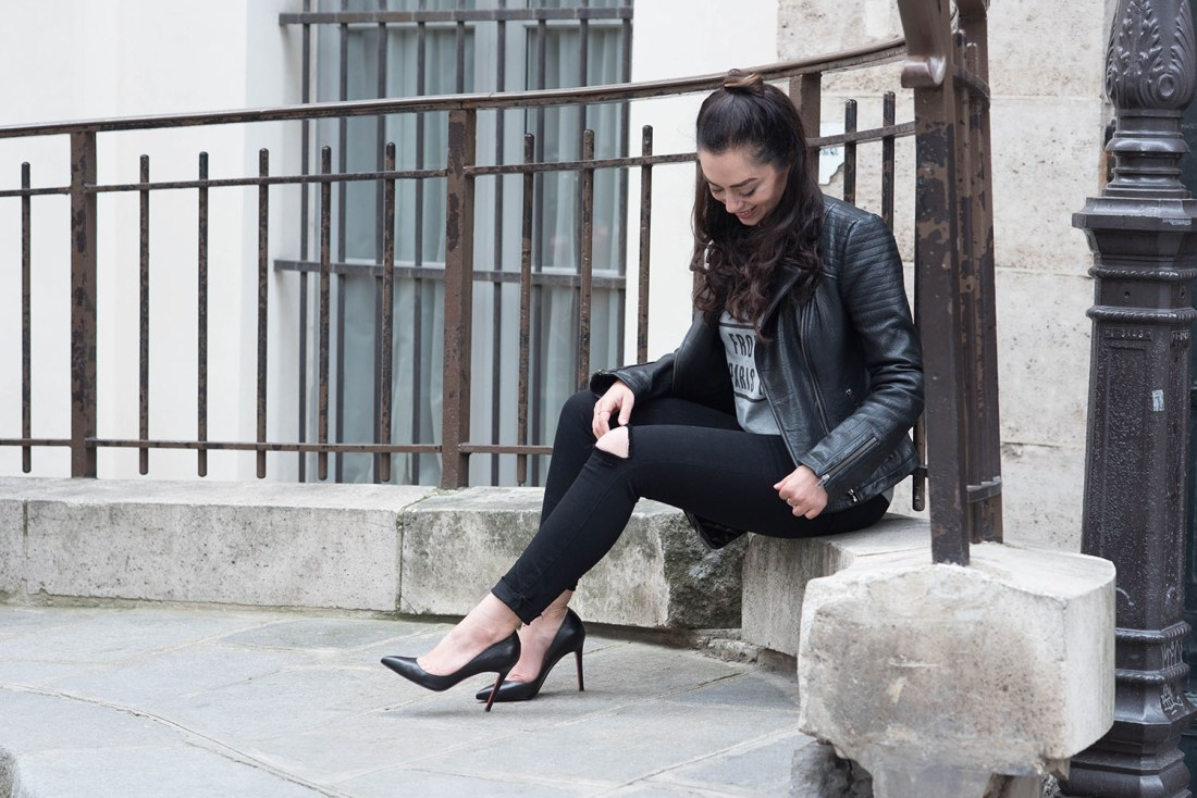 Fashion blogger Cee Fardoe of Coco & Vera sits at the Palais Royal in Paris wearing Paige jeans and Christian Louboutin heels