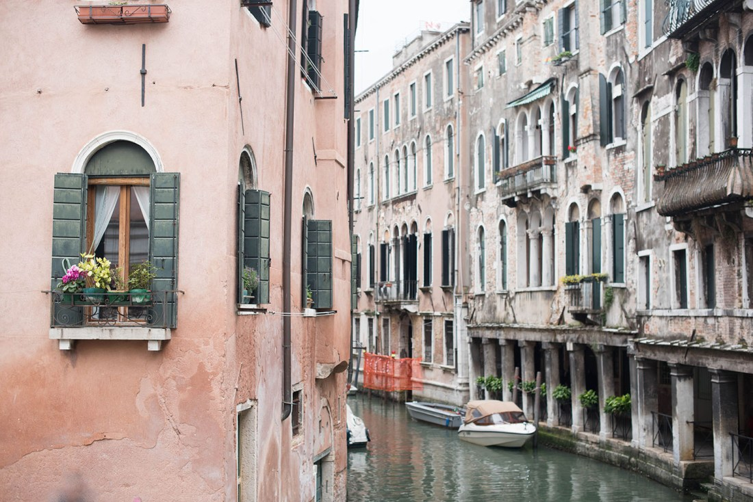 Photo of pink buildings with green and white shutters facing onto canal in Venice
