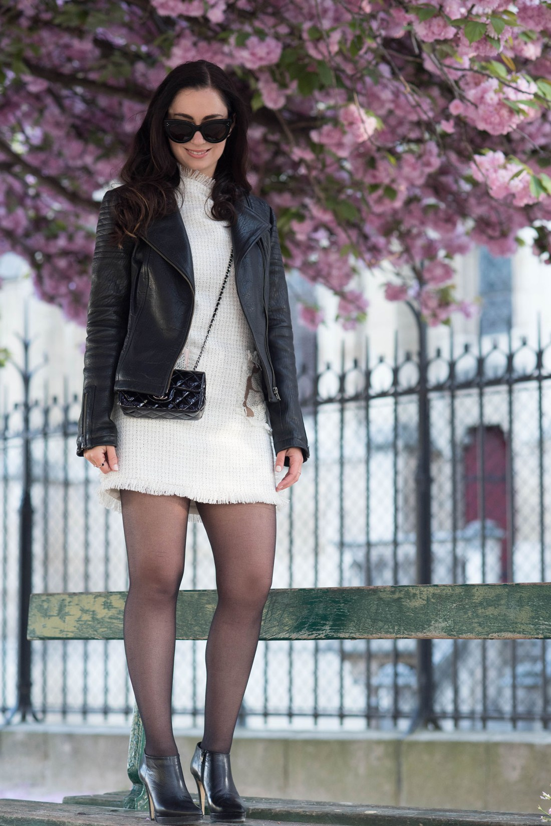 Fashion blogger Cee Fardoe of Coco & Vera stands on a bench wearing a Floriane Fosso dress and Chanel bag