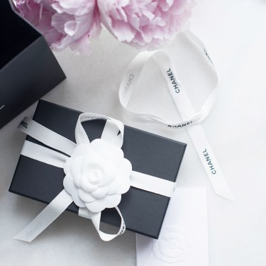 A black Chanel box on a marble table with pink peonies, arranged by style blogger Cee Fardoe of Coco & Vera