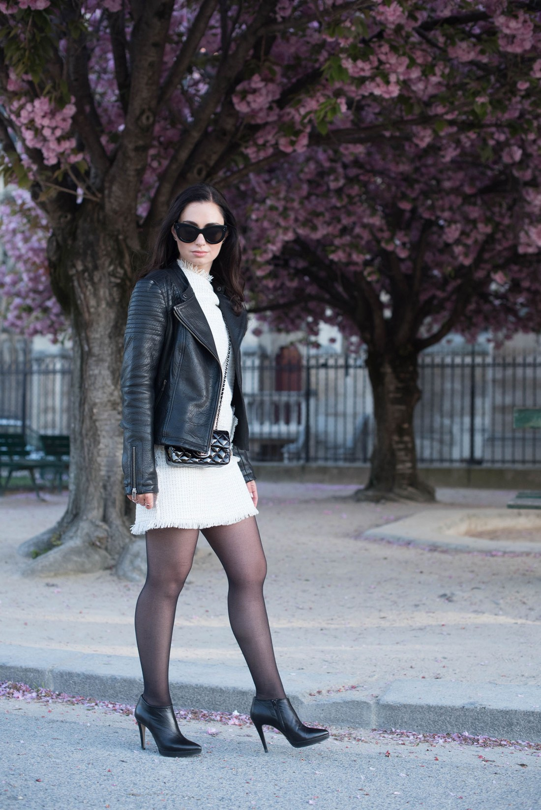 Fashion blogger Cee Fardoe of Coco & Vera walks on Ile de la Cite wearing a Floriane Fosso dress and Le Chateau boots