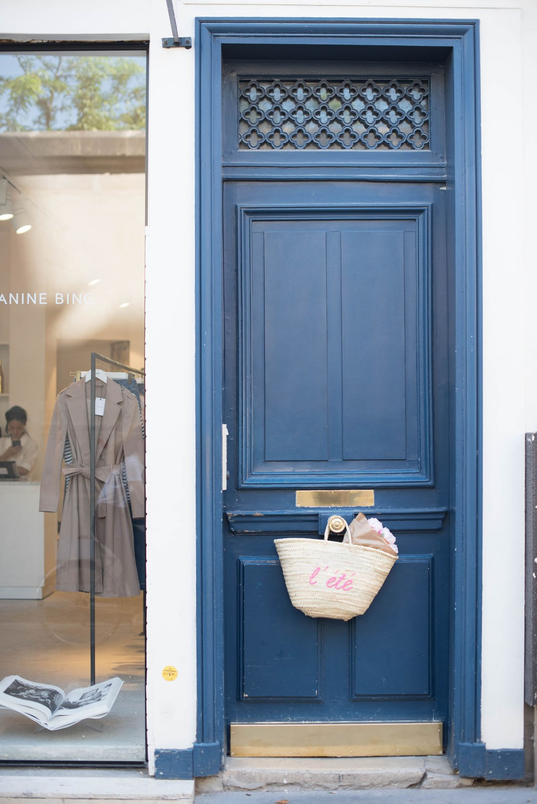 A Sezane straw tote full of pink peonies hangs on a blue door in le Marais, captured by travel blogger Cee Fardoe of Coco & Vera