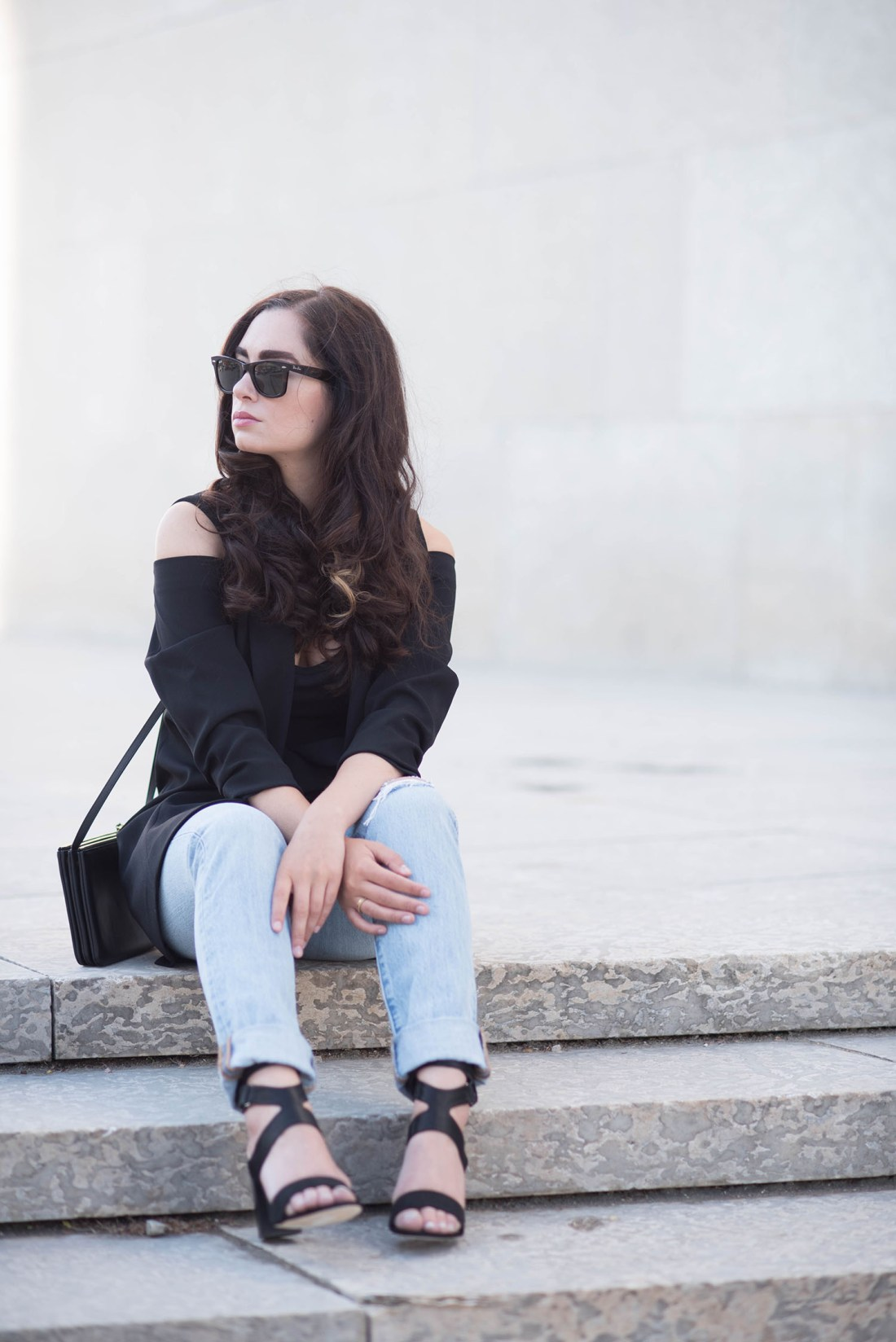 Fashion blogger Cee Fardoe of Coco & Vera sitting on the Winnipeg Art Gallery stairs wearing a black Ever New coat and Levis jeans