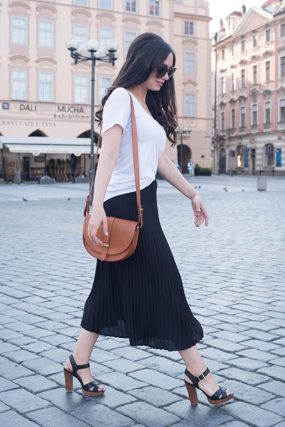Canadian fashion blogger Cee Fardoe of Coco & Vera walks through Old Town Square in Prague carrying a Sezane Claude bag and wearing a black Aritzia skirt