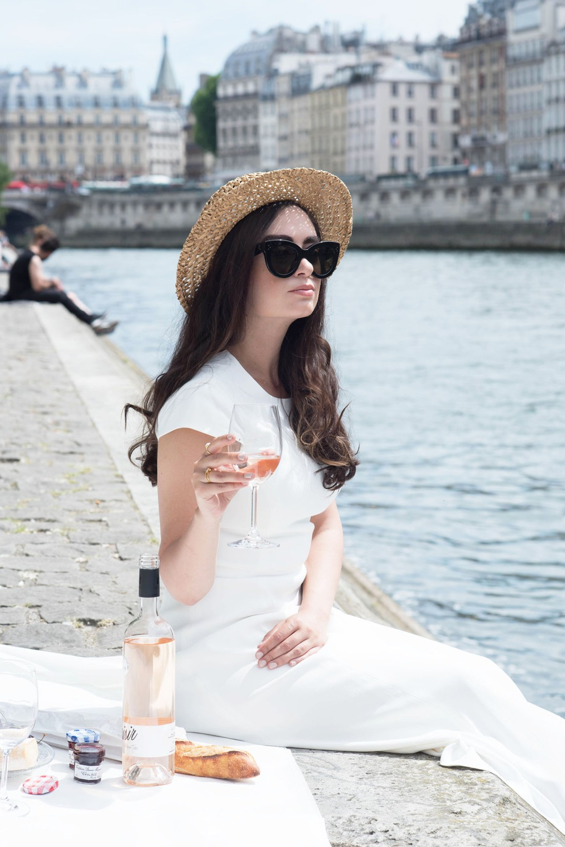 Style blogger Cee Fardoe of Coco & Vera sits on the banks of the Seine river in Paris wearing an Ivy & Oak white dress