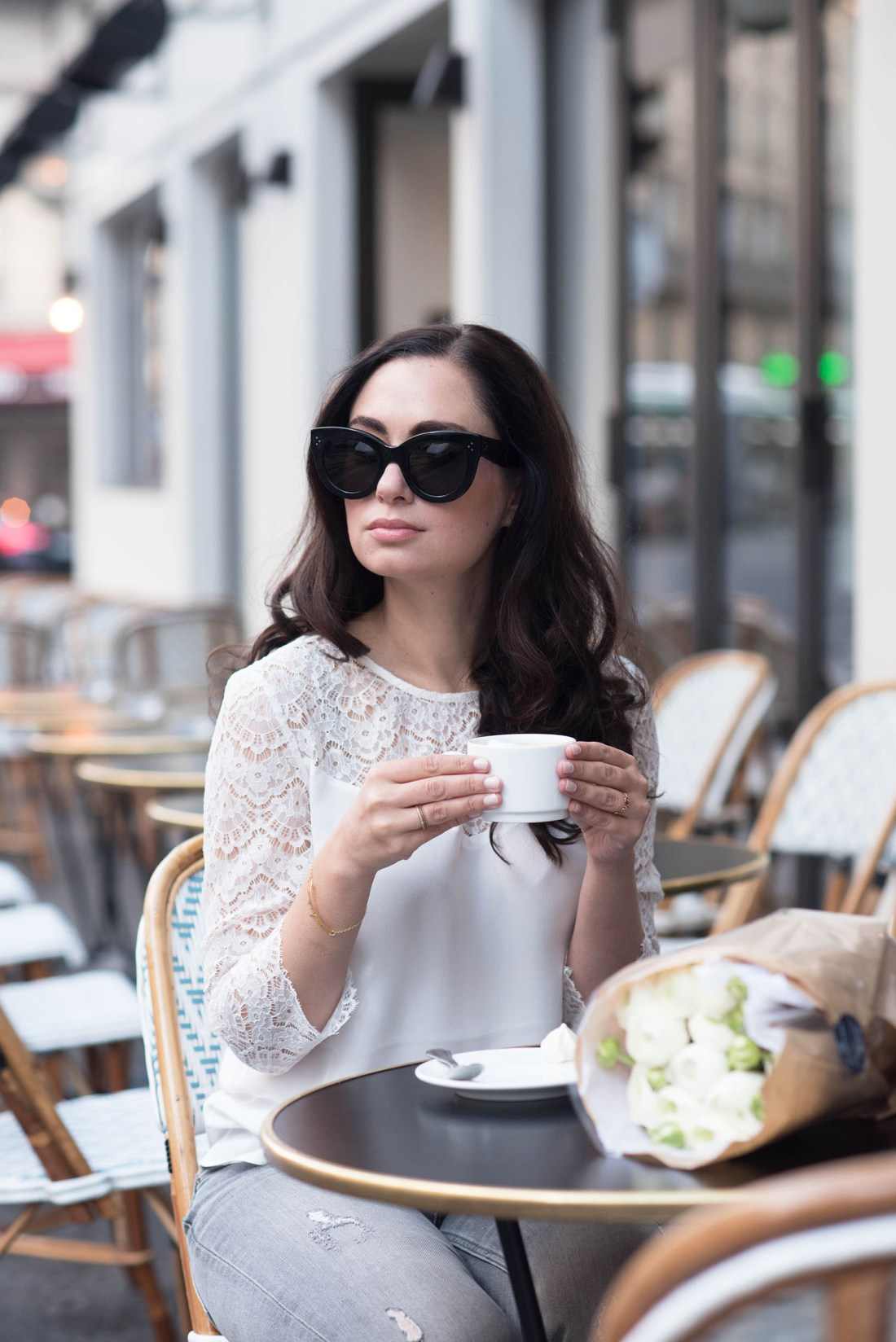 Winnipeg fashion blogger Cee Fardoe of Coco & Vera sits outside at Maison Marie in Paris, holding her coffee cup and wearing a Sezane blouse