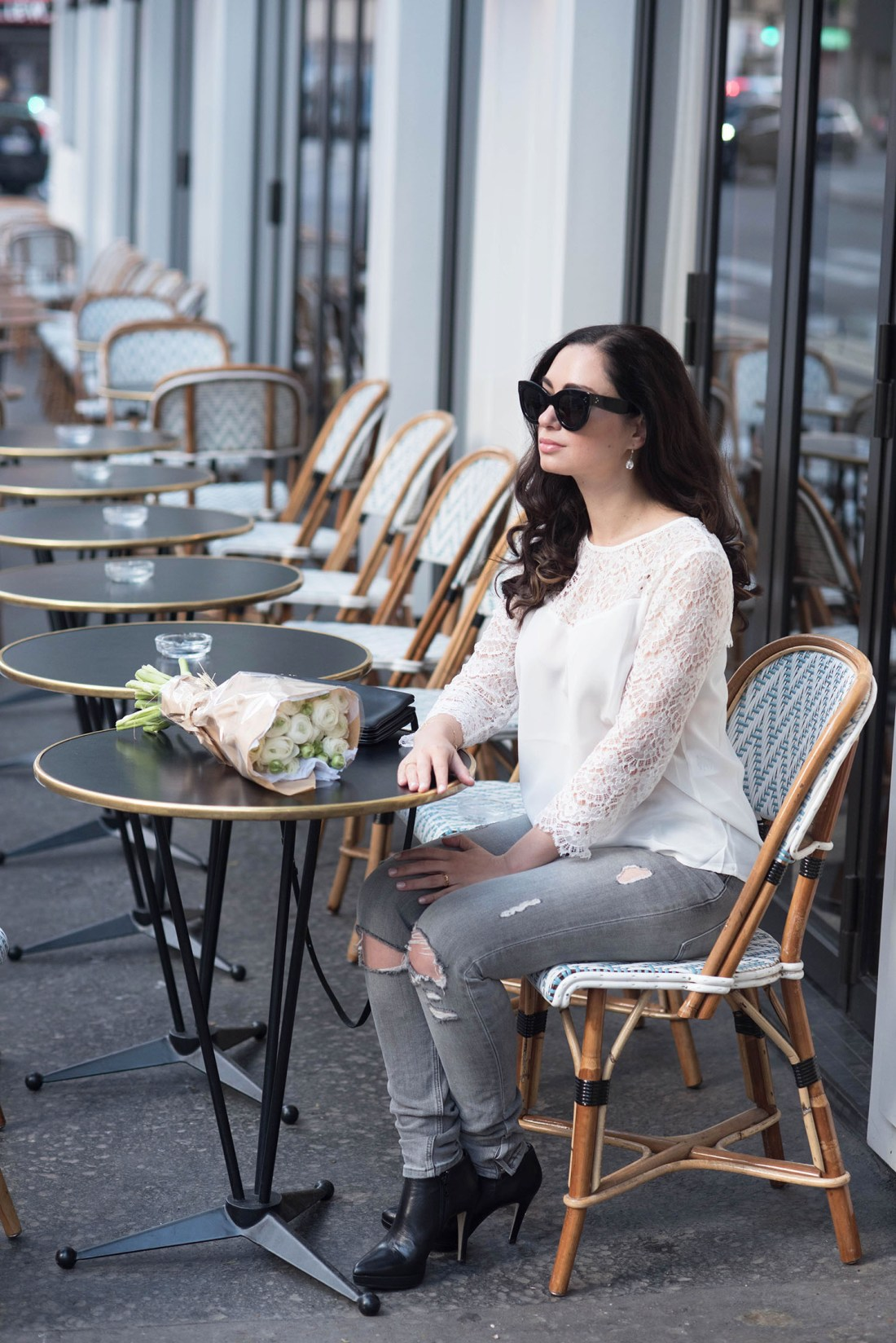 Fashion blogger Cee Fardoe of Coco & Vera sits at cafe Maison Marie in Paris wearing a white silk and lace Sezane blouse