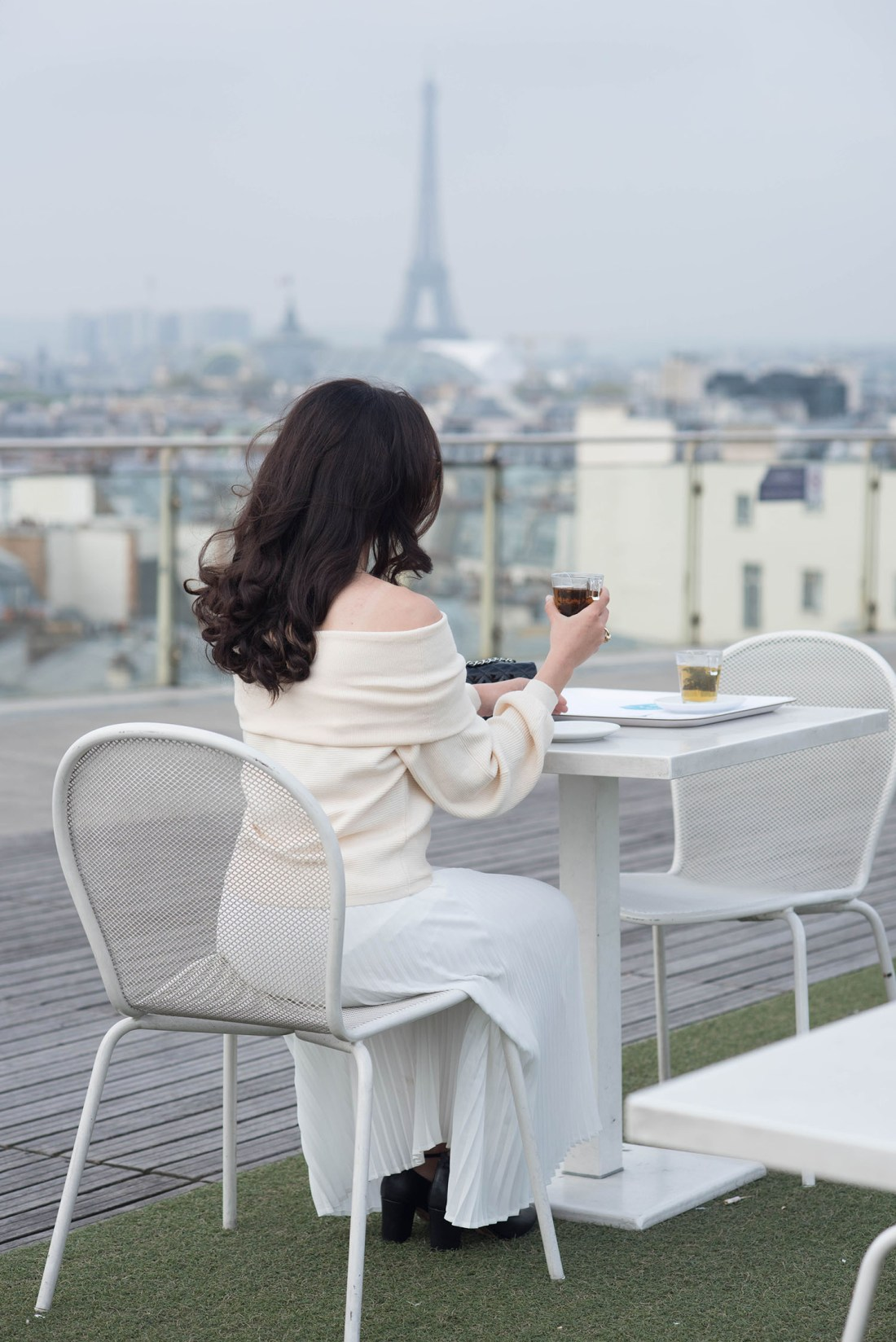 Fashion blogger Cee Fardoe sits at the rooftop cafe at Printemps in Paris, wearing a blush Zara sweater and white pleated Aritzia skirt