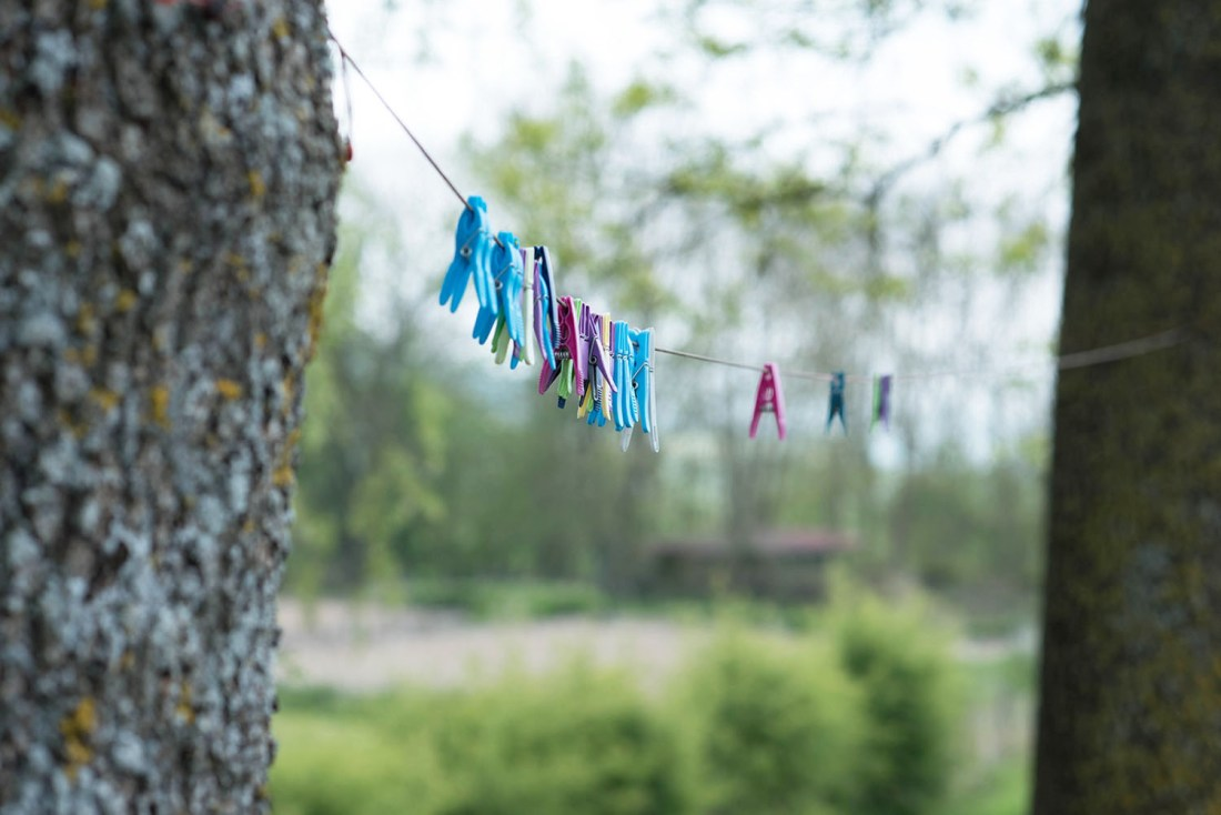 Colourful clothes pegs hang on a line in between two trees in the Burgundy region of France, as captured by top travel blogger Cee Fardoe of Coco & Vera