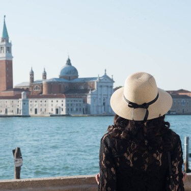 Fashion blogger Cee Fardoe of Coco & Vera stands on a Venetian bridge looking out over the Grand Canal wearing a Galeries Lafayette straw hat and Gentlefawn lace dress