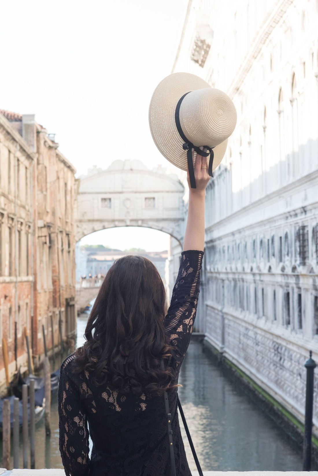 Canadian fashion blogger Cee Fardoe of Coco & Vera holds up her Galeries Lafayette straw hat on a bridge in Venice