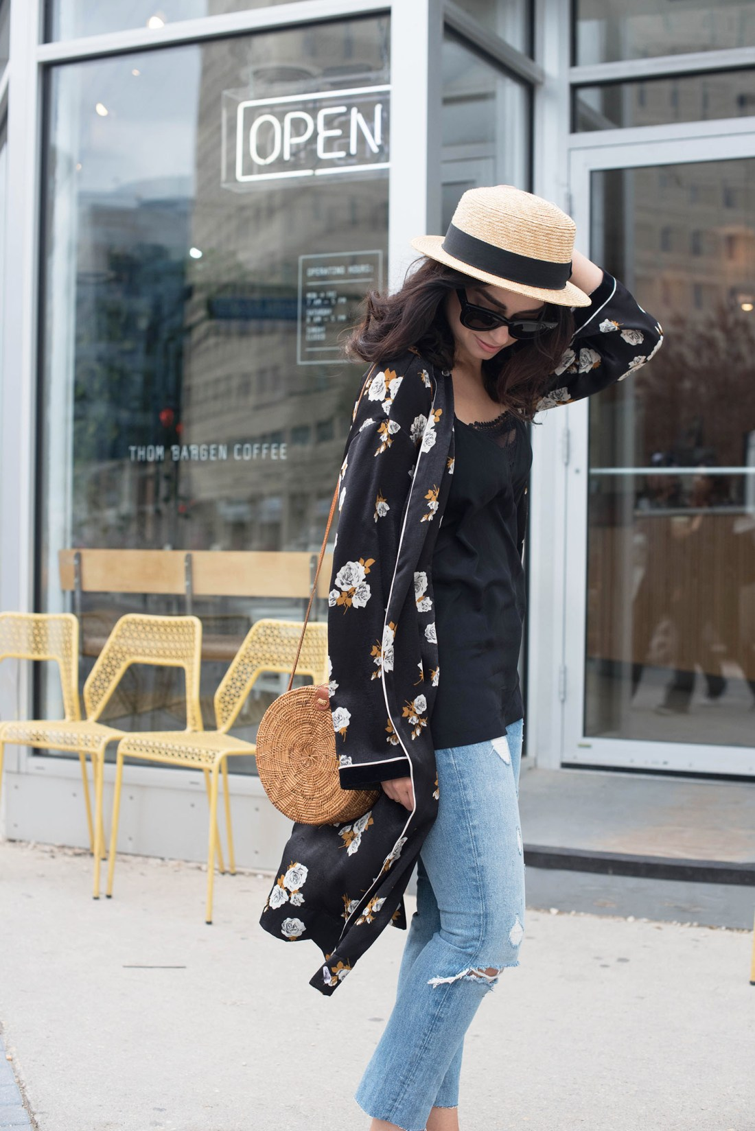 Fashion blogger Cee Fardoe of Coco & Vera holds onto her straw hat outside Thom Bargan coffee, wearing Grlfrnd Karolina jeans and a Zara black kimono
