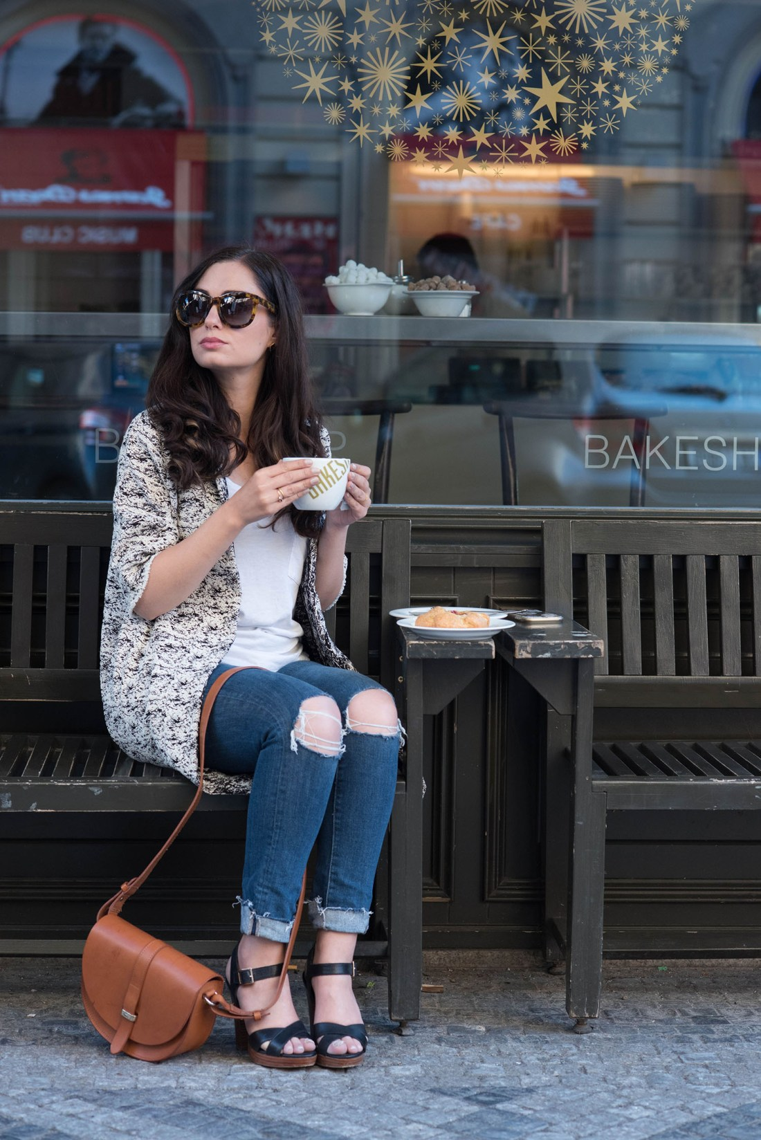 Fashion blogger Cee Fardoe of Coco & Vera sits at a cafe in Prague wearing a Floriane Fosso jacket and Le Chateau sandals