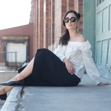 Fashion blogger Cee Fardoe of Coco & Vera sits in an old loading bay wearing a L'Academie off-shoulder blouse, RayBan Wayfarer sunglasses and black Aritzia culottes