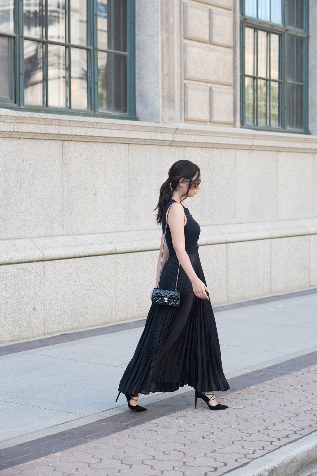 Winnipeg fashion blogger Cee Fardoe of Coco & Vera walks in the Exchange District wearing a black ALC gown and carrying a Chanel extra mini handbag