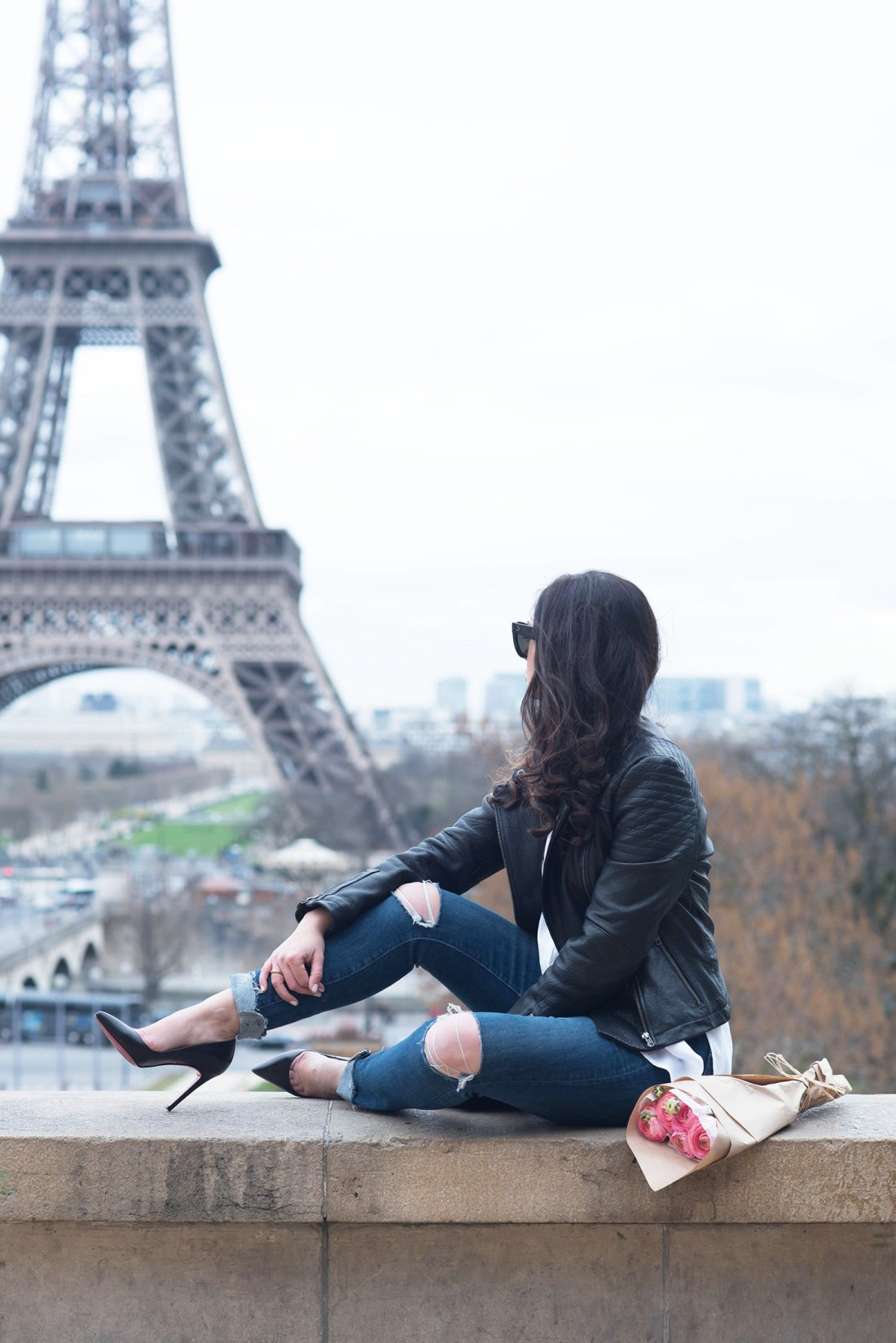 Fashion blogger Cee Fardoe of Coco & Vera sits at Place Trocadero in front of th Eiffel Tower wearing Paige Hoxton jeans and a Cupcakes and Cashmere leather jacket