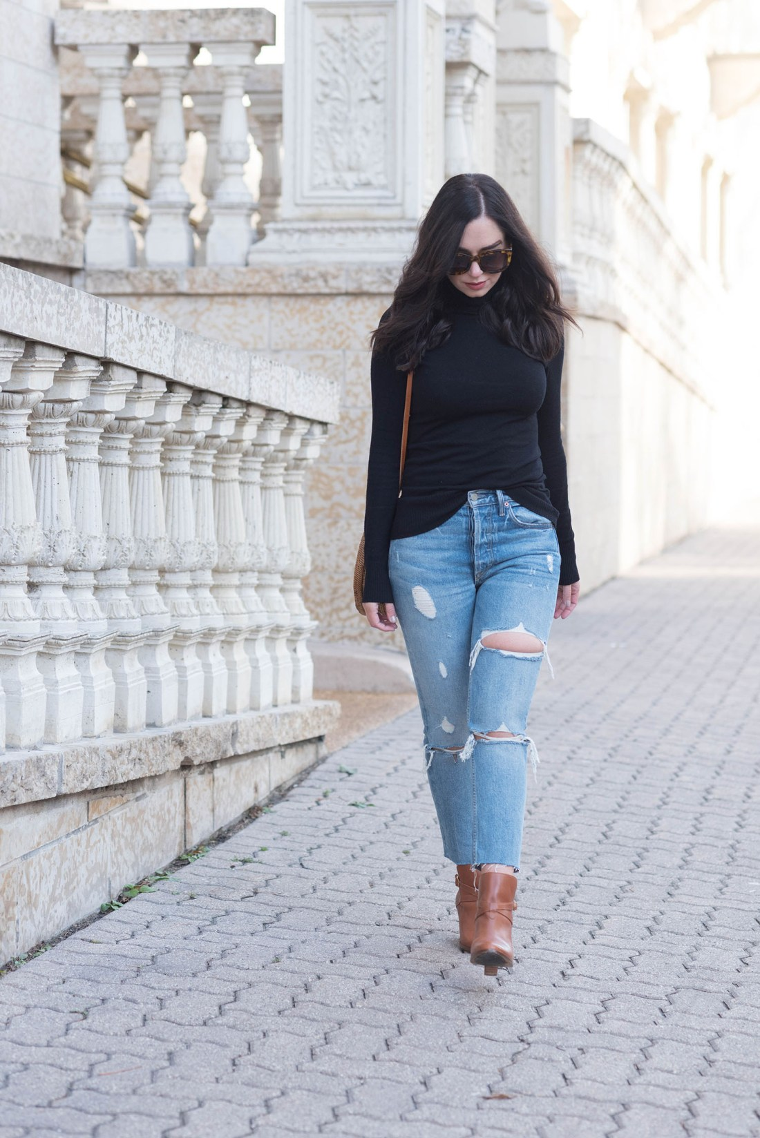 Fashion blogger Cee Fardoe of Coco & Vera walks by Fort Garry Place in Winnipeg wearing Grlfrnd jeans and Sezane ankle boots