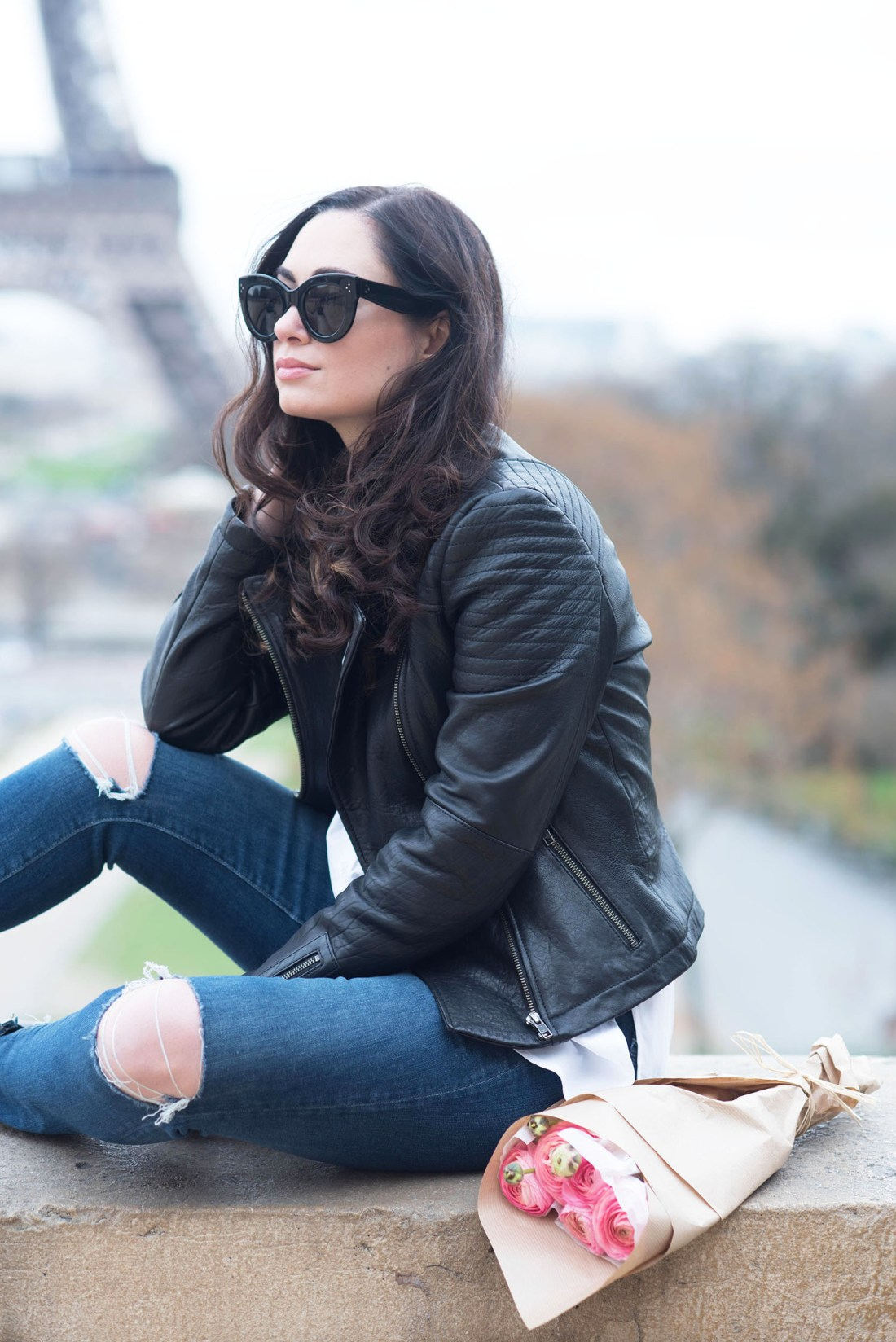 Portrait of Winnipeg fashion blogger Cee Fardoe of Coco & Vera sitting at Place Trocadero wearing a Cupcakes and Cashmere leather jacket with Celine Audrey sunglasses