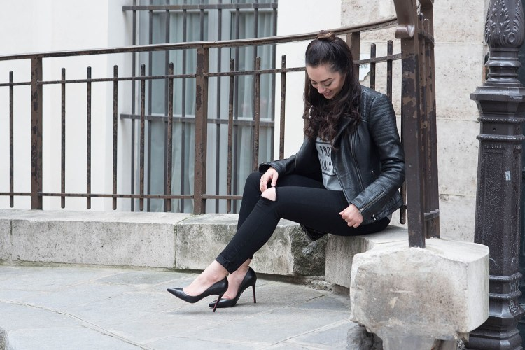 Winnipeg fashion blogger Cee Fardoe of Coco & Vera sits outside the Palais Royal in Paris wearing a Cupcakes & Cashmere leather jacket and Christian Louboutin Pigalle pumps