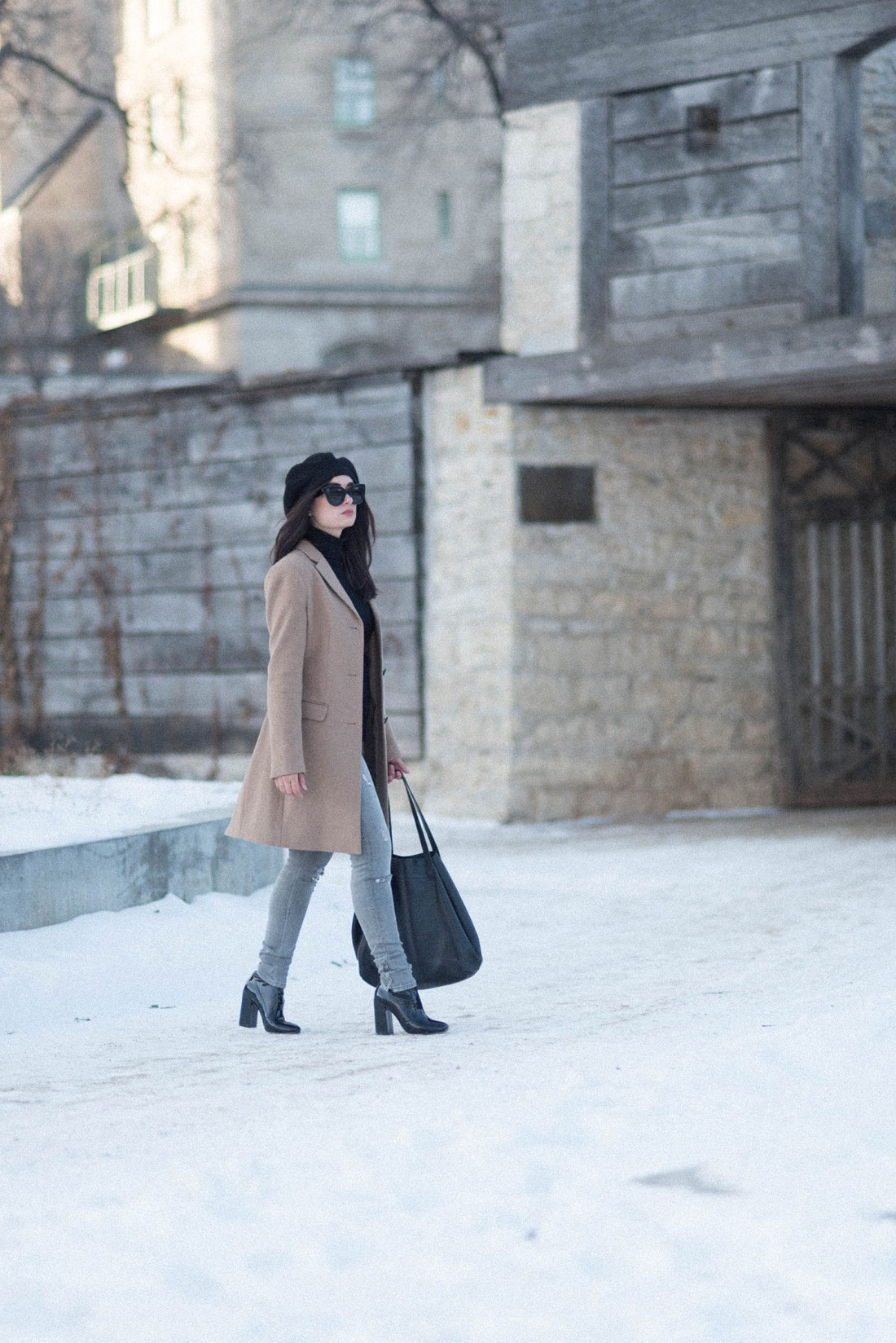 Fashion blogger Cee Fardoe of Coco & Vera walks through the ruins of Fort Garry in Winnipeg wearing a Uniqlo camel coat and Raye patent ankle boots