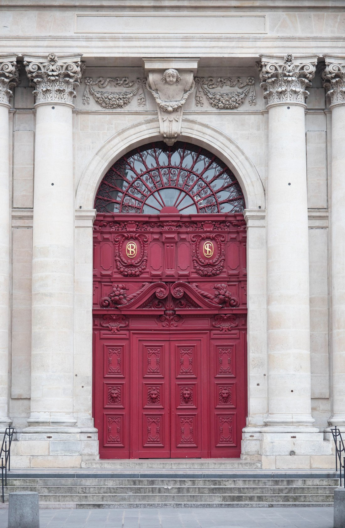 The ornate red door of a cathedral on rue de Rivoli in Paris, as photographed by Winnipeg travel blogger Cee Fardoe of Coco & Vera