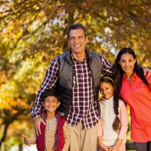 61655533 - portrait of happy family standing at park during autumn