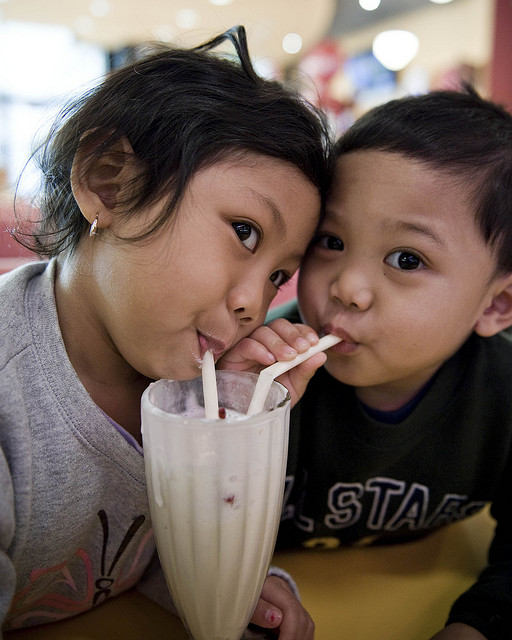 Two children sharing a milkshake
