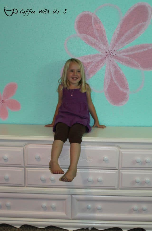 A bright wall turquoise wall color with pink flowers painted on, & some cute accessories make for a fun flower power girl's bedroom!
