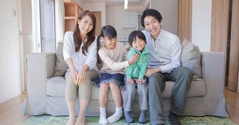 Família japonesa sentada no sofá