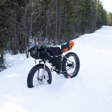 My own ti fatbike, resting in deeper snow with my gear for winter bikepacking trips in the frame bag, front bag, and seat bag.