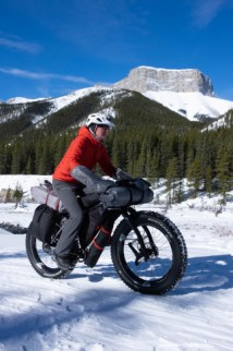 My friend Guy riding his bike on some snow with his very tidily loaded bike and a mountain in the background