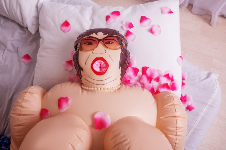 Inflatable,Sex,Doll,Strewed,With,Petals,Of,Roses.