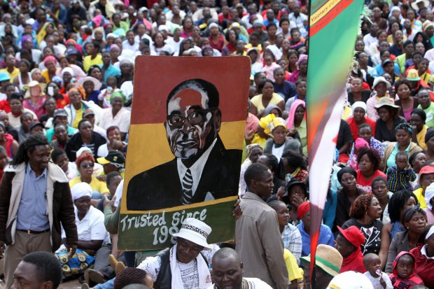 FILE - In Wednesday, July 20, 2016 file photo, thousands of Mugabe supporters carry his portrait while gathering at the party headquarters in Harare. Veterans of Zimbabwe's independence war made a significant break with President Robert Mugabe for the first time Thursday, July 21, 2016, calling him dictatorial, manipulative and egocentric. (AP Photo/Tsvangirayi Mukwazhi, File)