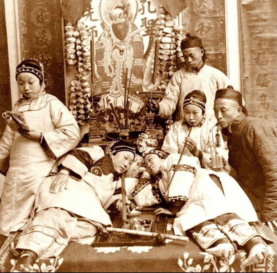 This photo depicting opium smoking was posed in a studio for a stereoview card, circa 1900.