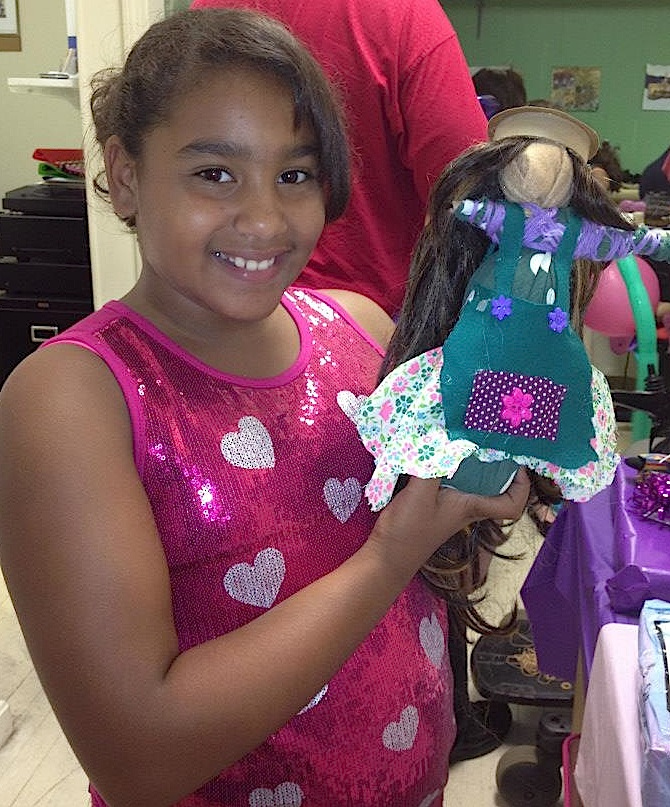 A girl poses with the African wrap doll she made at a class at the National Black Doll Museum. From the museum's Facebook page.