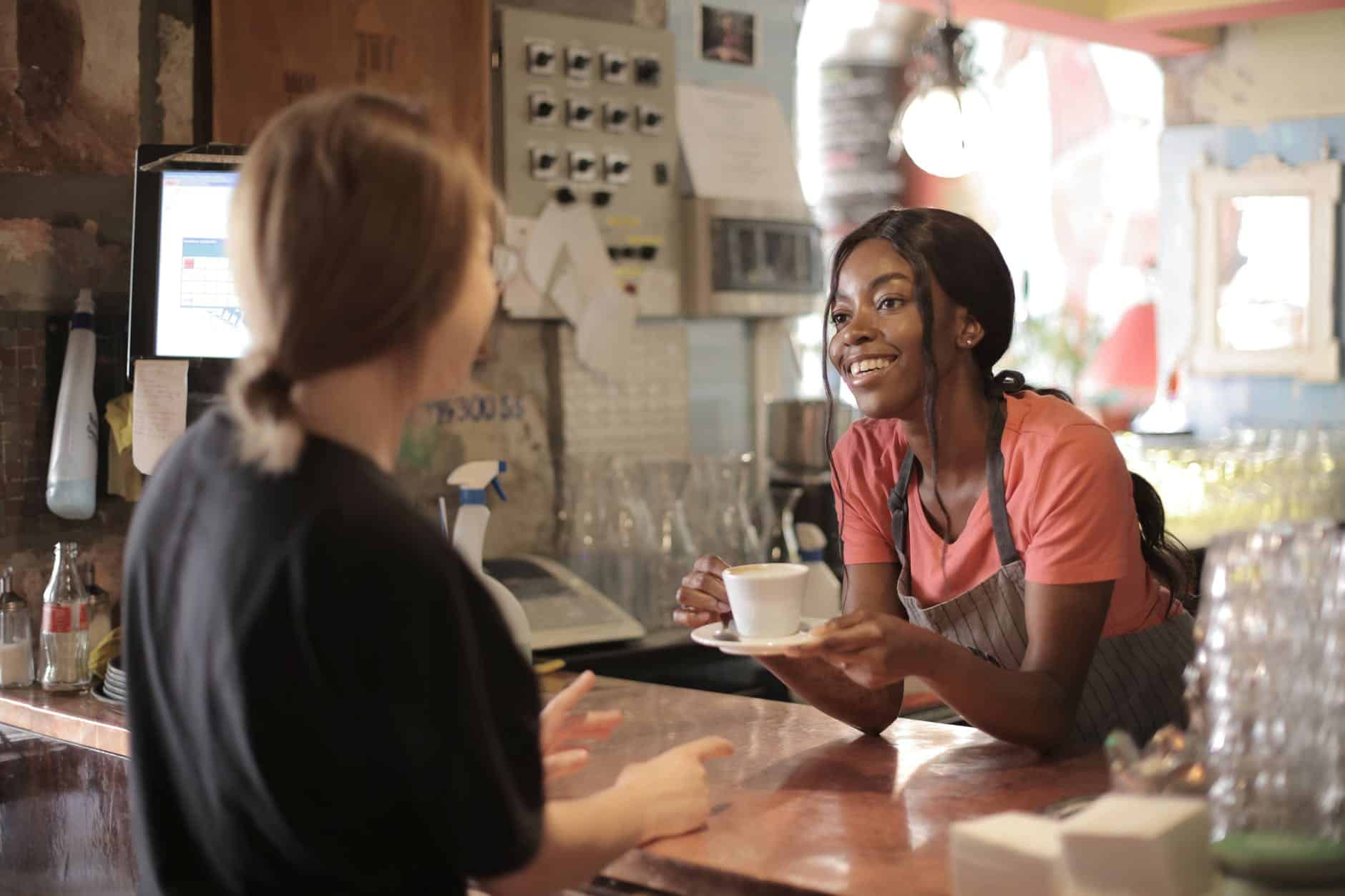 delighted black female barista serving coffee in cup in cafe