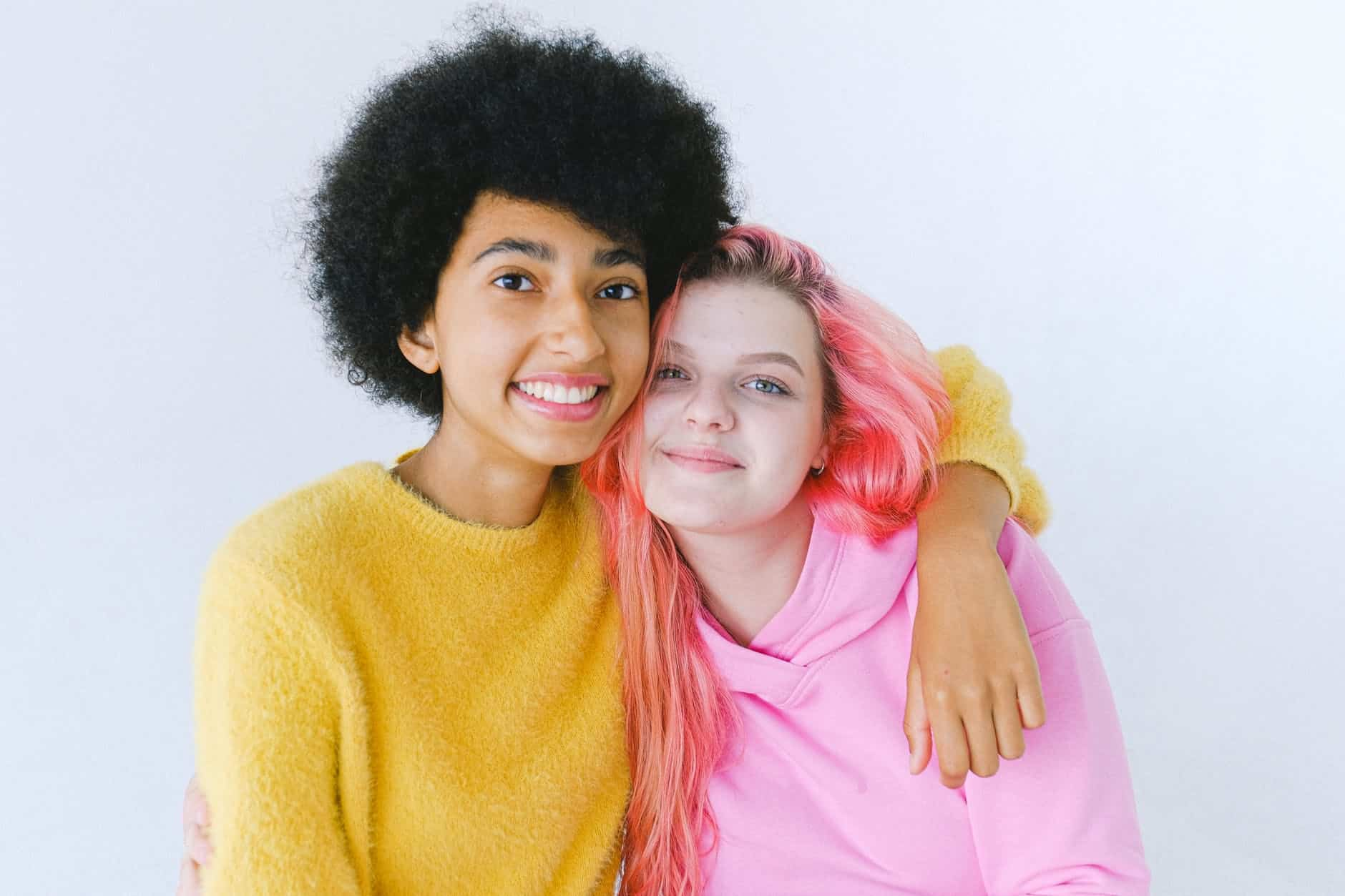 glad diverse teenage best friends in bright outfit embracing