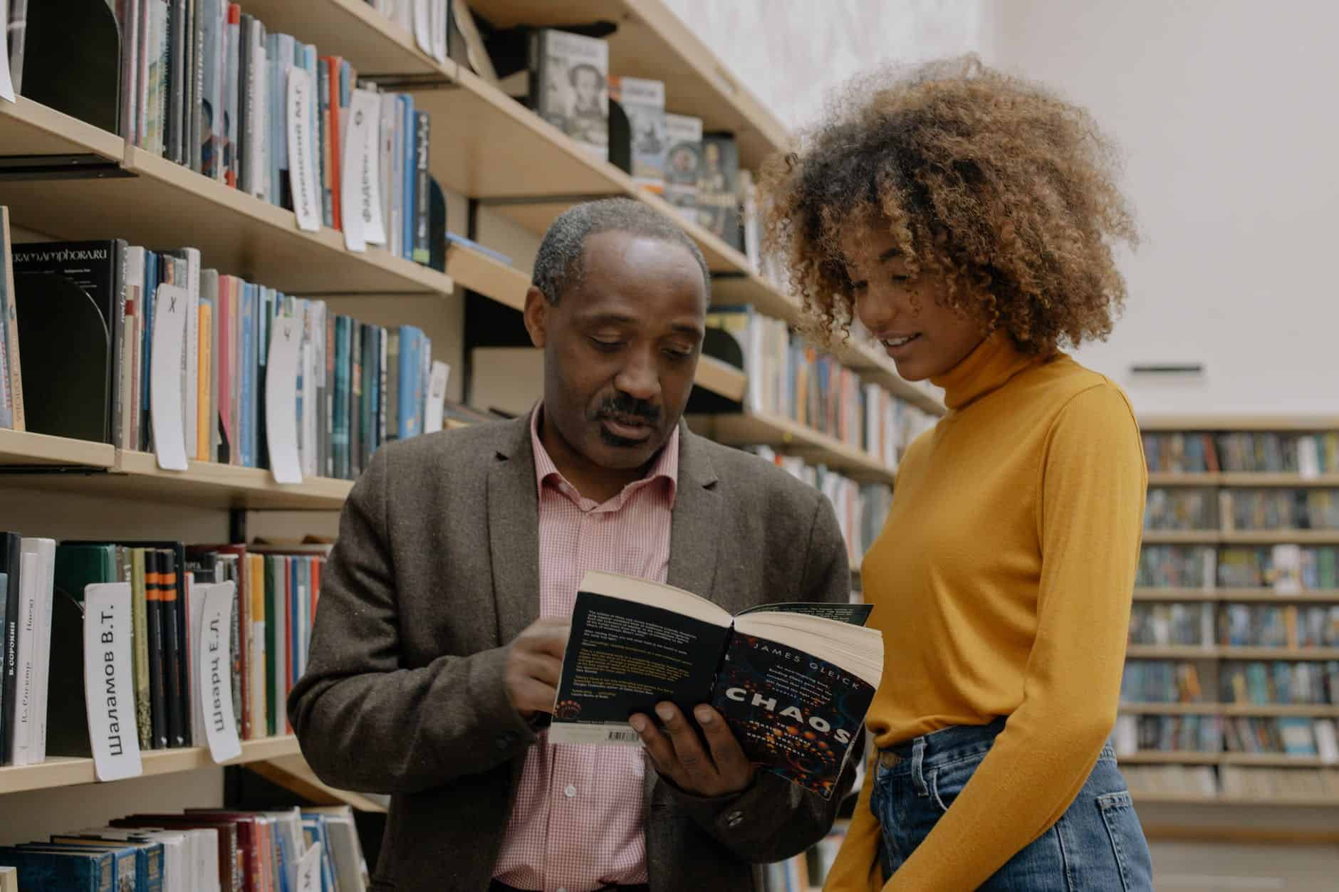 man in yellow sweater holding book beside woman in brown sweater