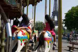 Twins on a Paris carrousel with the Eiffel Tower in the background