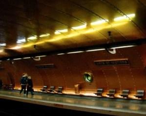 Two people walking along the platform of Metro Arts Metier