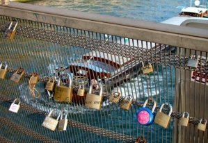 Padlocks on the Passerelle de Léopold-Sédar-Senghor, formerly known as Passerelle Solférino bridge with passing peniche/barge