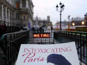 """Partial book cover """"Intoxicating Paris"""" by PJ Adams with Metro, Hotel de Ville plaza and Notre-Dame in the background"""